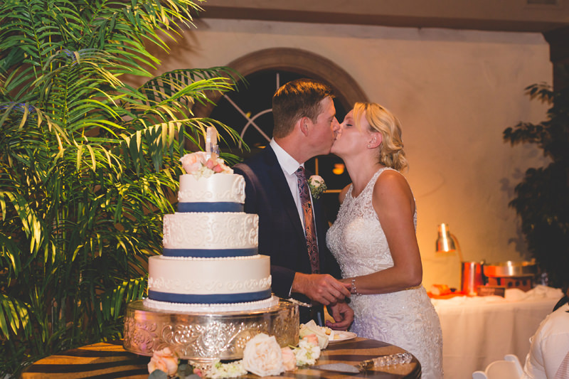 Bride and Groom kissing after feeding each other wedding cake at their reception