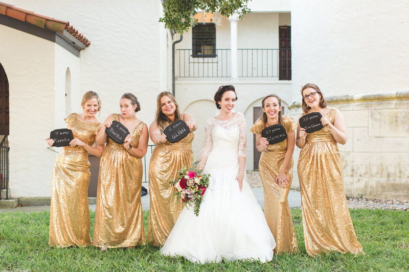 Bridesmaids in gold sequins dresses holding chalkboard signs at Rollins College wedding