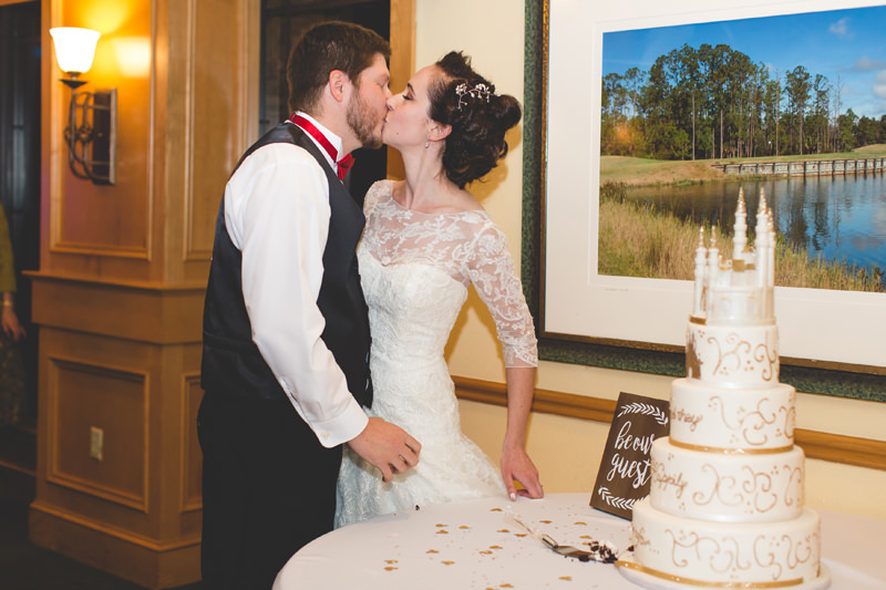 Bride and Groom kissing beside their white and gold Disney inspired wedding cake with Cinderella castle