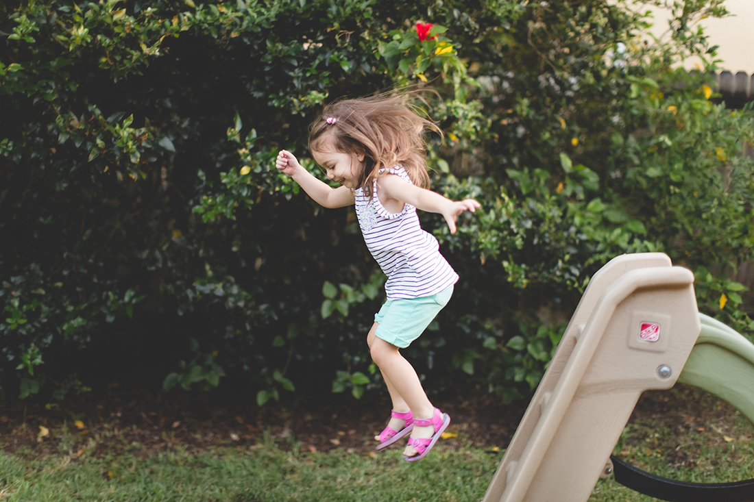 little girl jumping from slide photo - orlando documentary family photographer - Jaime DiOrio.jpg