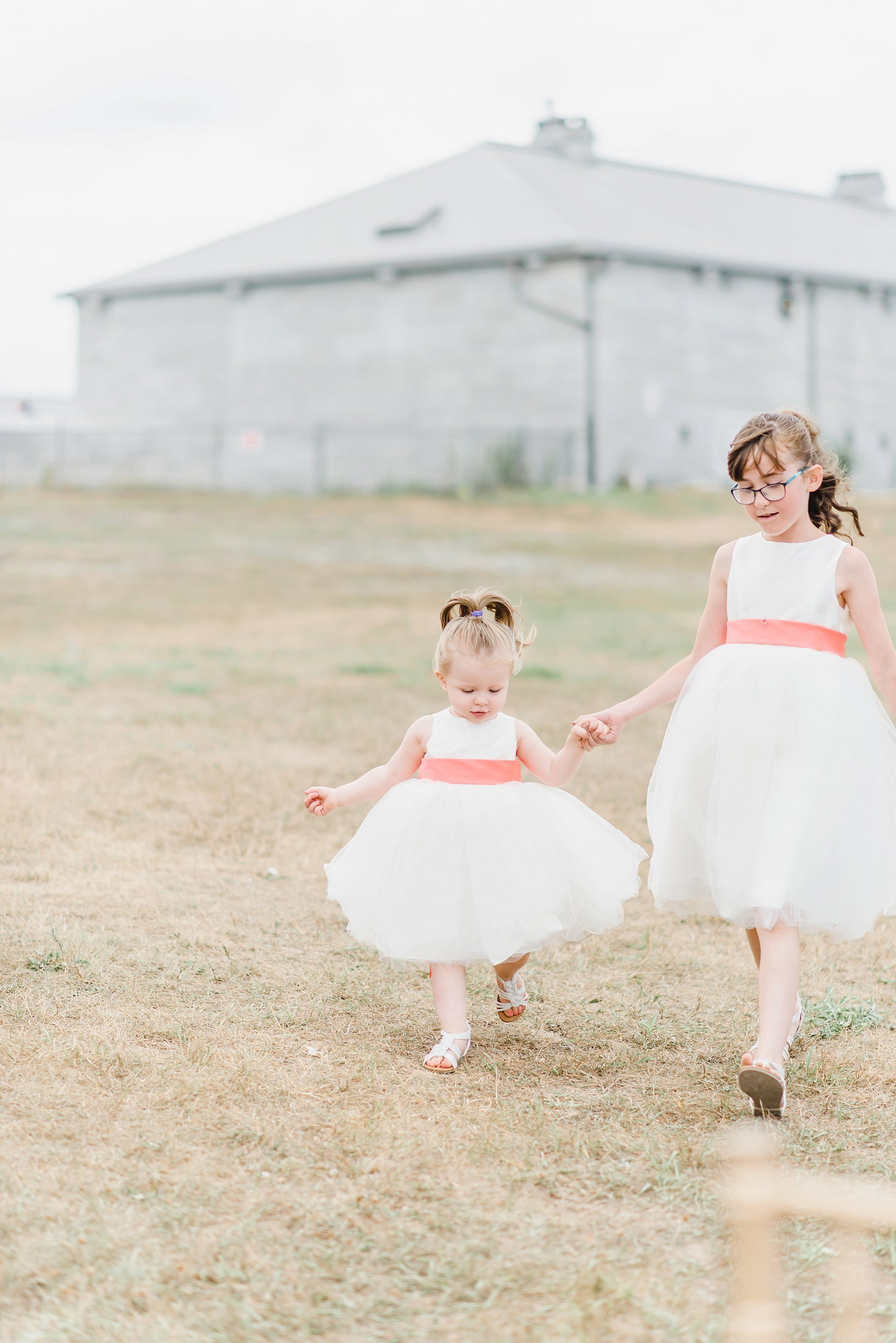 Here's Emma and Tim's adorable daughter frolicking towards them during the ceremony as one of their flower girls, with her cousin's hand in hers.