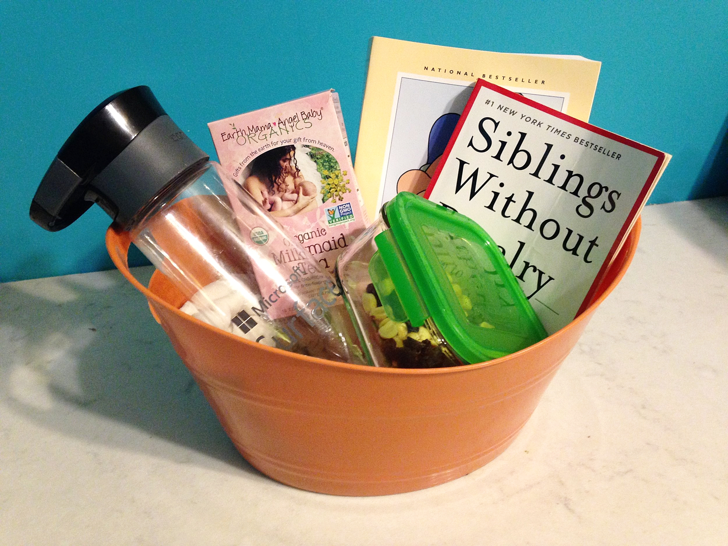 Some great items to have in your feeding basket to have on hand. (Image: An orange basket holding a water bottle, trail mix, some books, and a box of milkmaid tea).