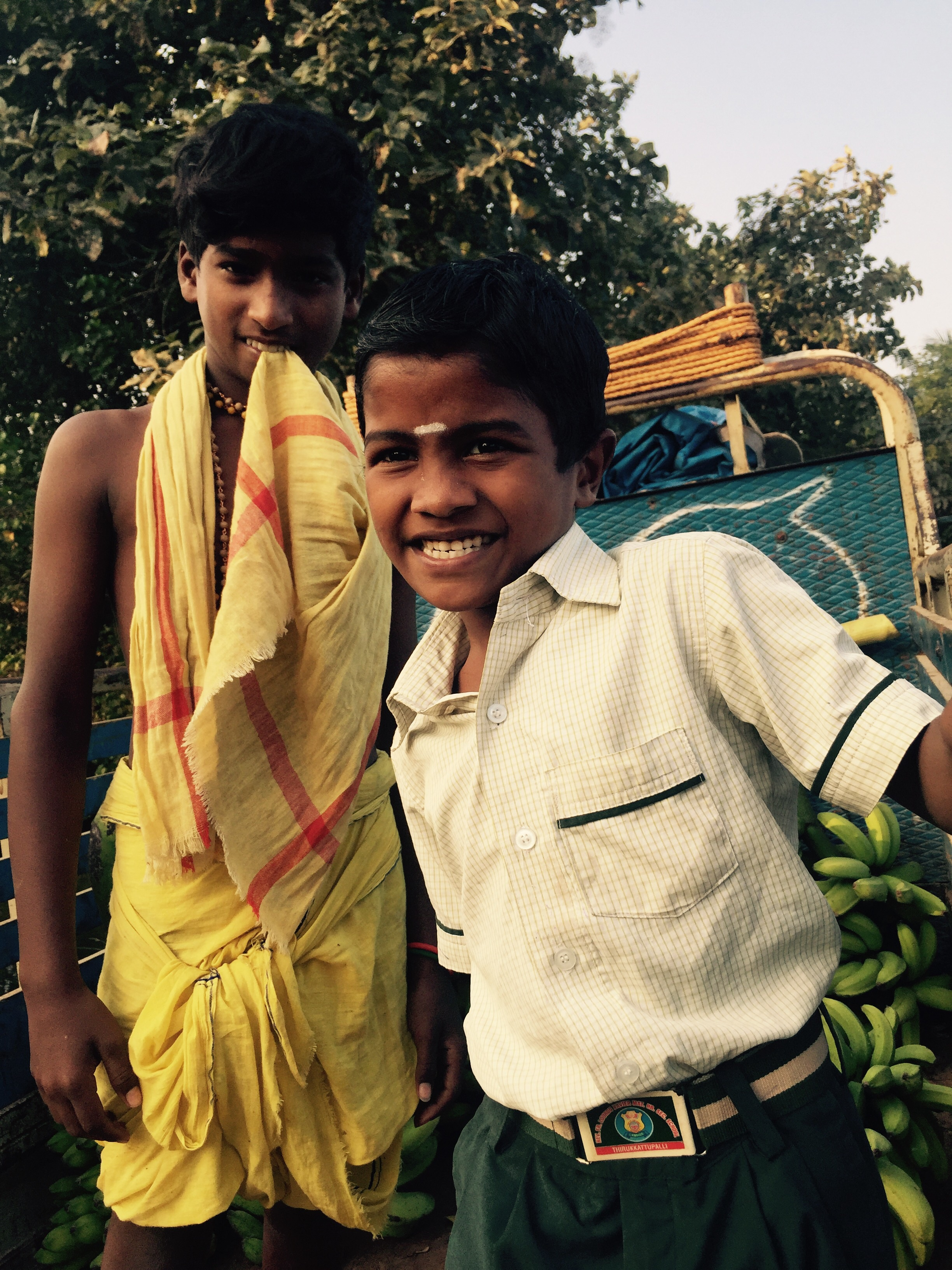 Two Kids. One going to school, the other out picking bananas in the fields