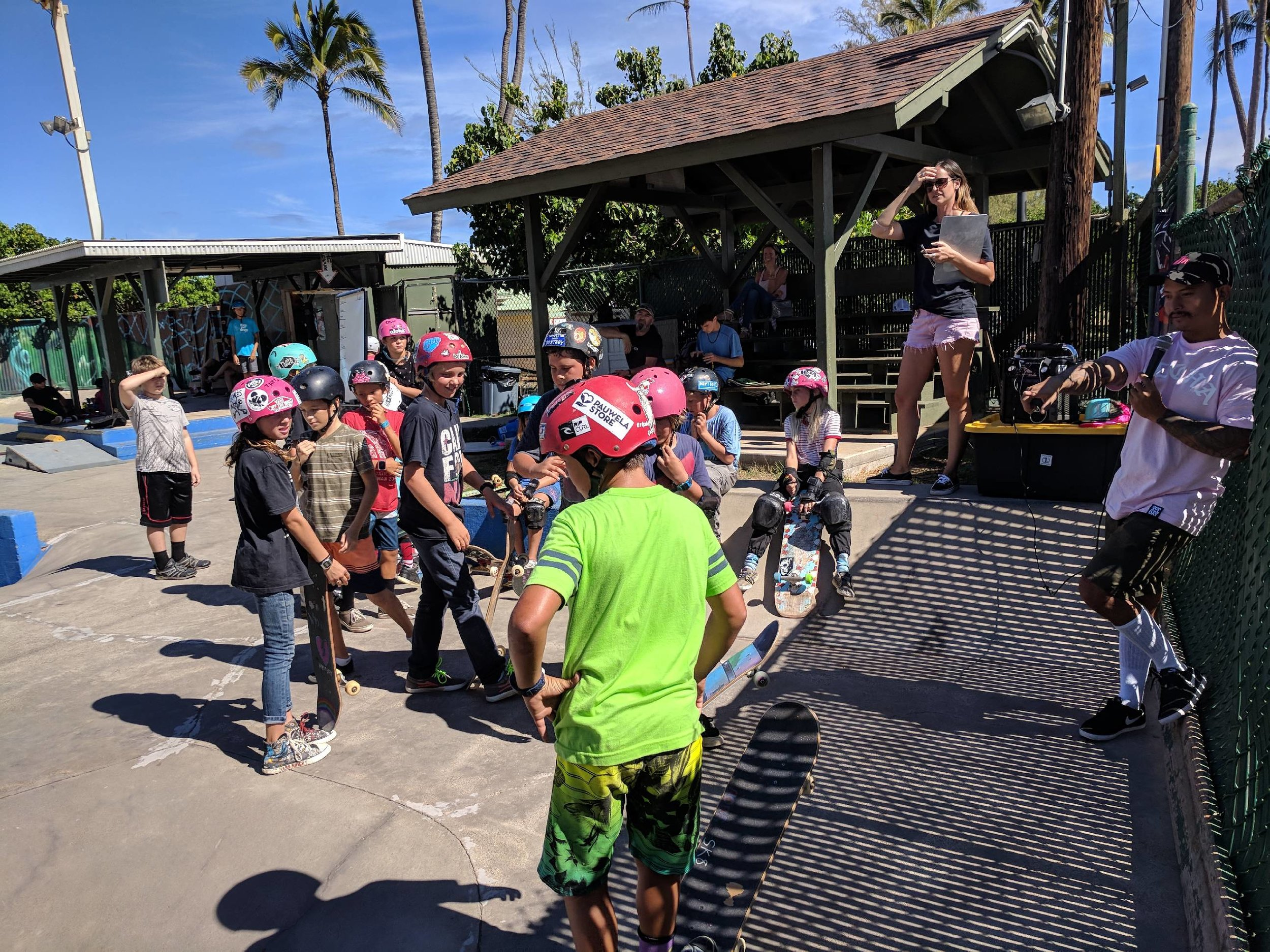 """Sam of One Love,& Lo from Paia Youth & Cultural Center, pictured here bringing the fun &keeping track of points as students played """"Simons Says, Skate!"""""""