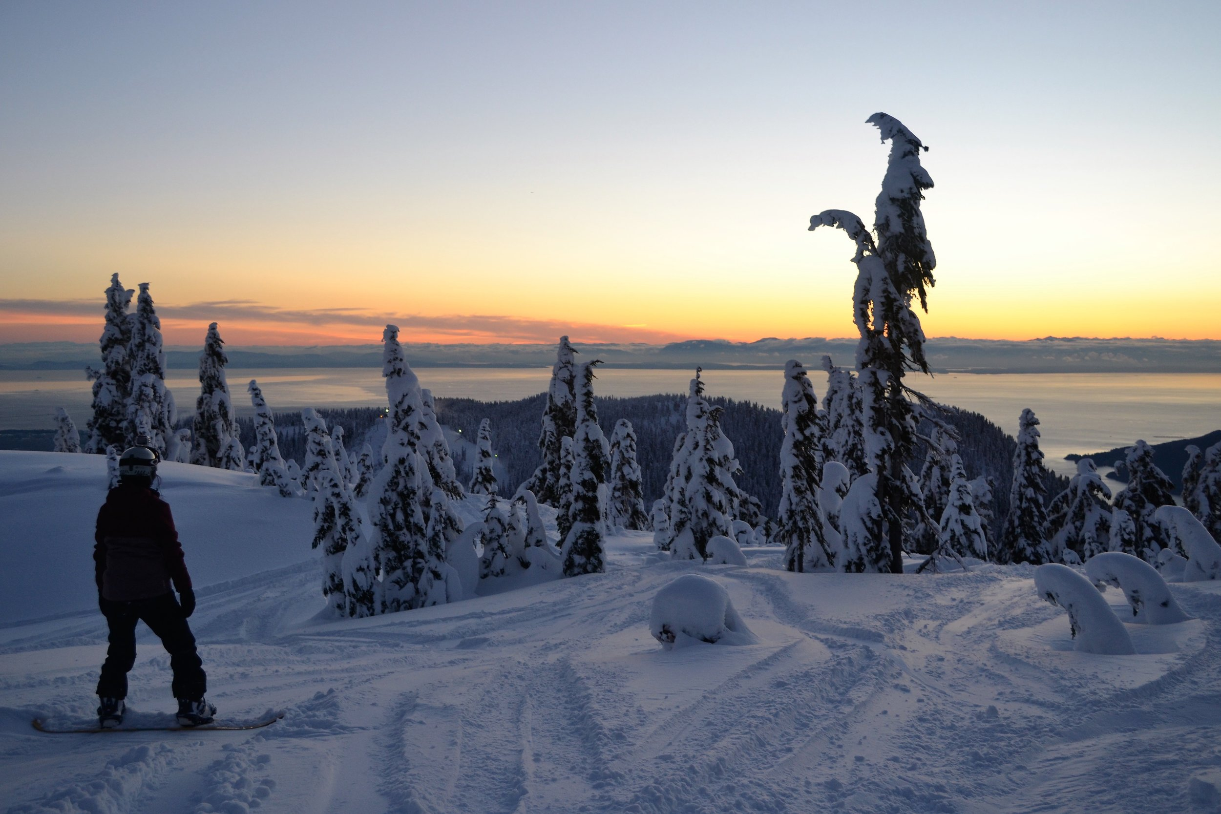 Snowboarder overlooking the ocean in Vancouver during sunset