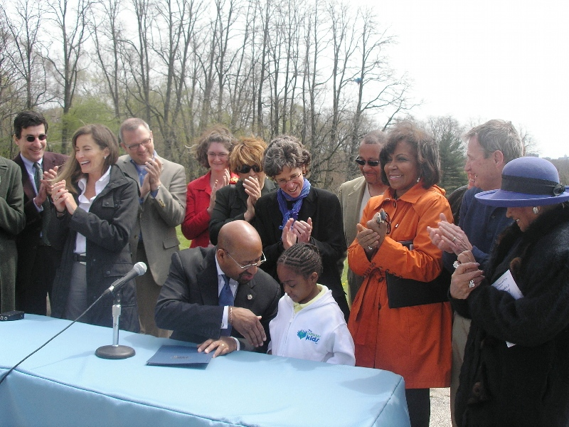 Commissioners celebrate as the Mayor signs the bill