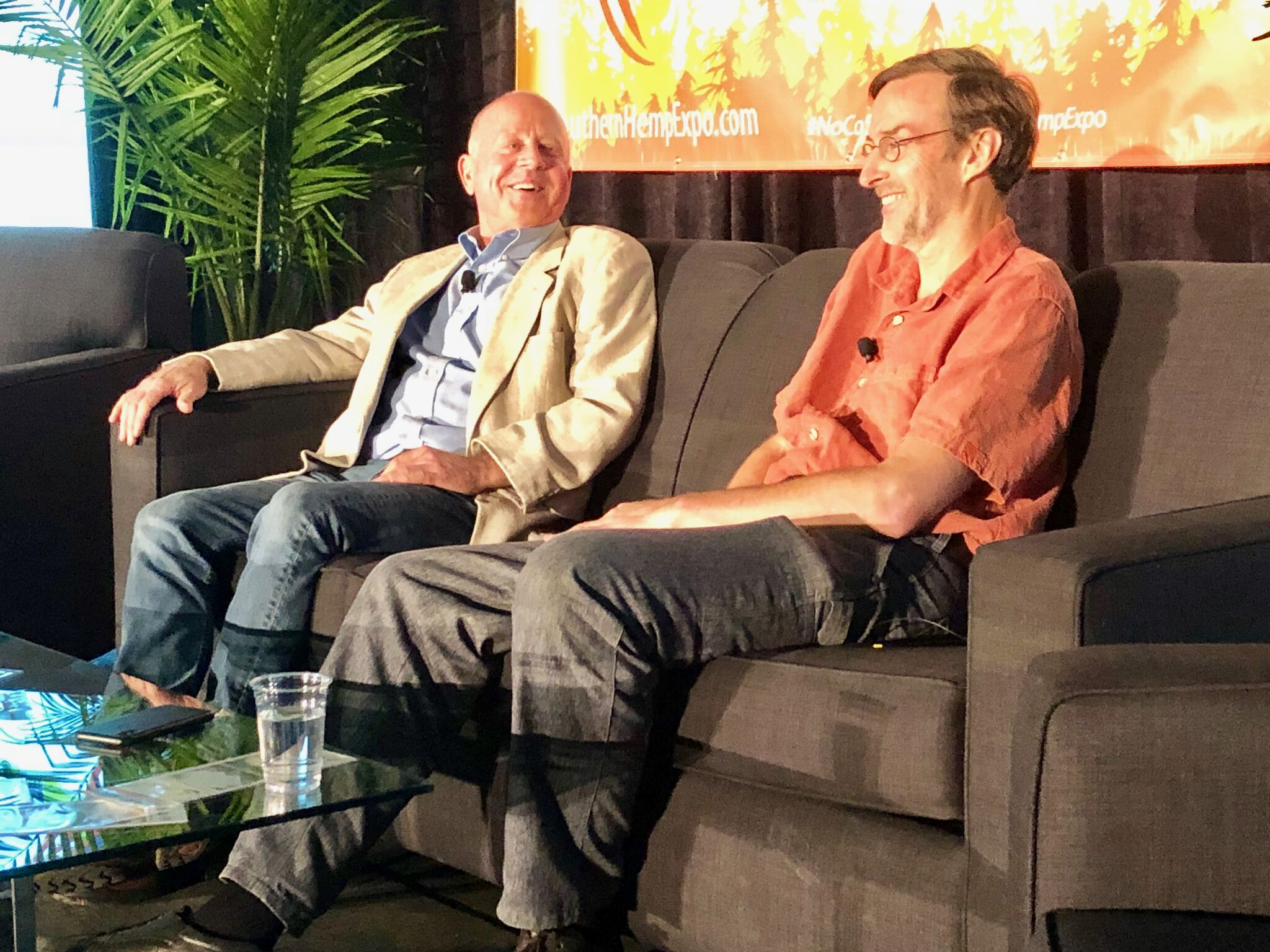 Pioneering hemp farmer Joe Hickey and John Roulac, founder of Nutiva and Re: Botanicals, share a laugh on stage at the Southern Hemp Expo Business Conference.