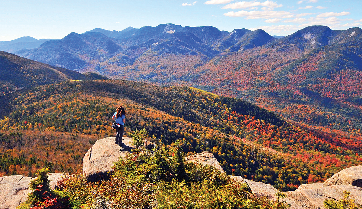 A hiker surveys the Adirondack High Peaks looking southwest from the summit of Noonmark.  Dave Kraus/KrausGrafik.com