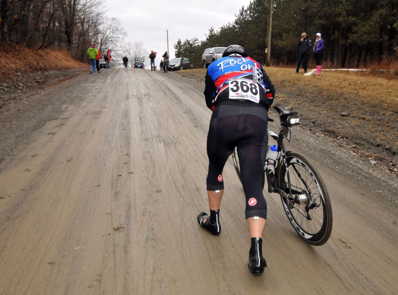 """The jersey may say """"Rock On,"""" but this rider is having a bit or trouble living up to the motto on Juniper Swamp Hill.  2014 - © Dave Kraus"""