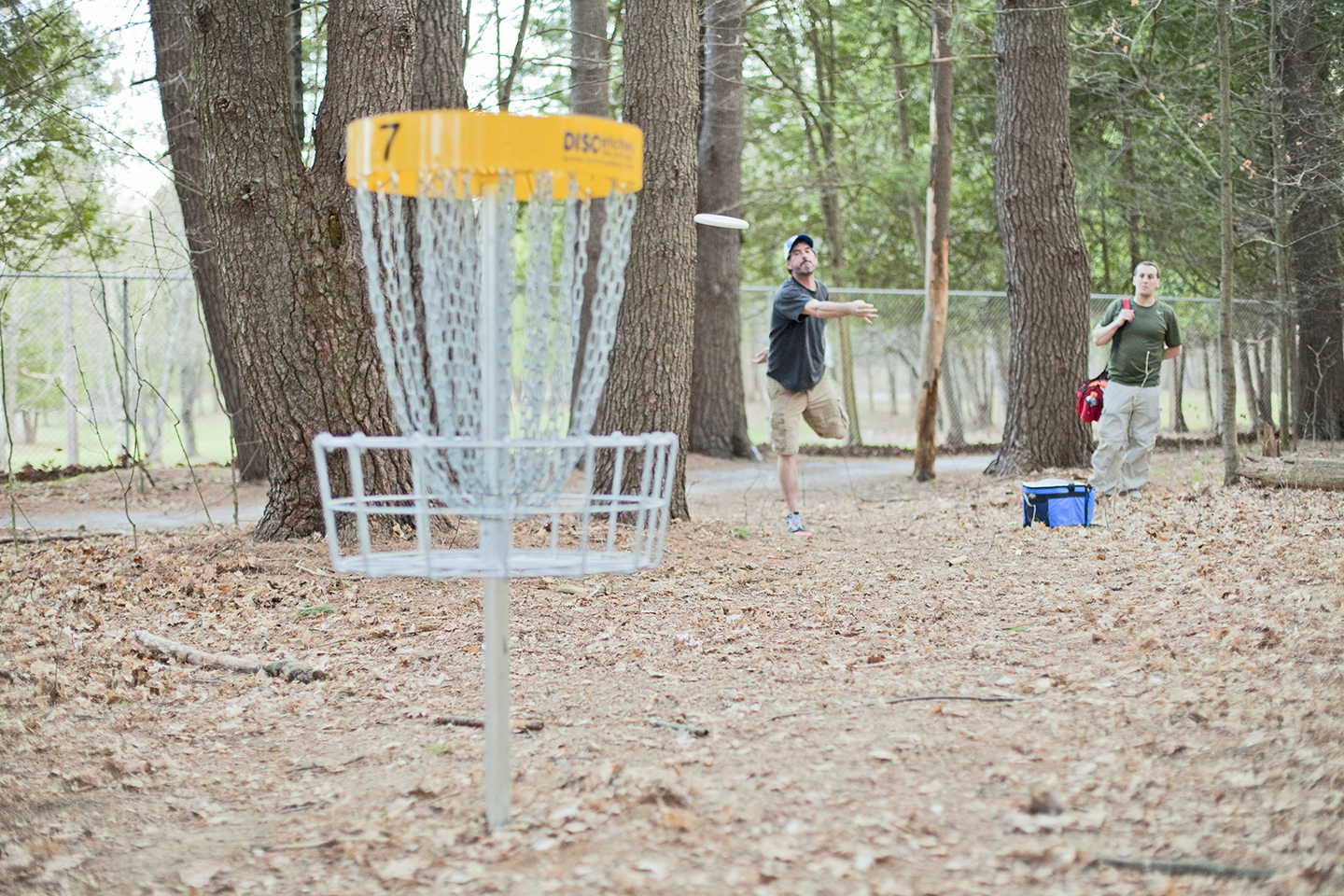 Tim DeFranco looks on as Jamin Totino attempts to sink a lengthy putt on Hole 7 at Saratoga Spa State Park's disc golf course.     Anthony Aquino Photography