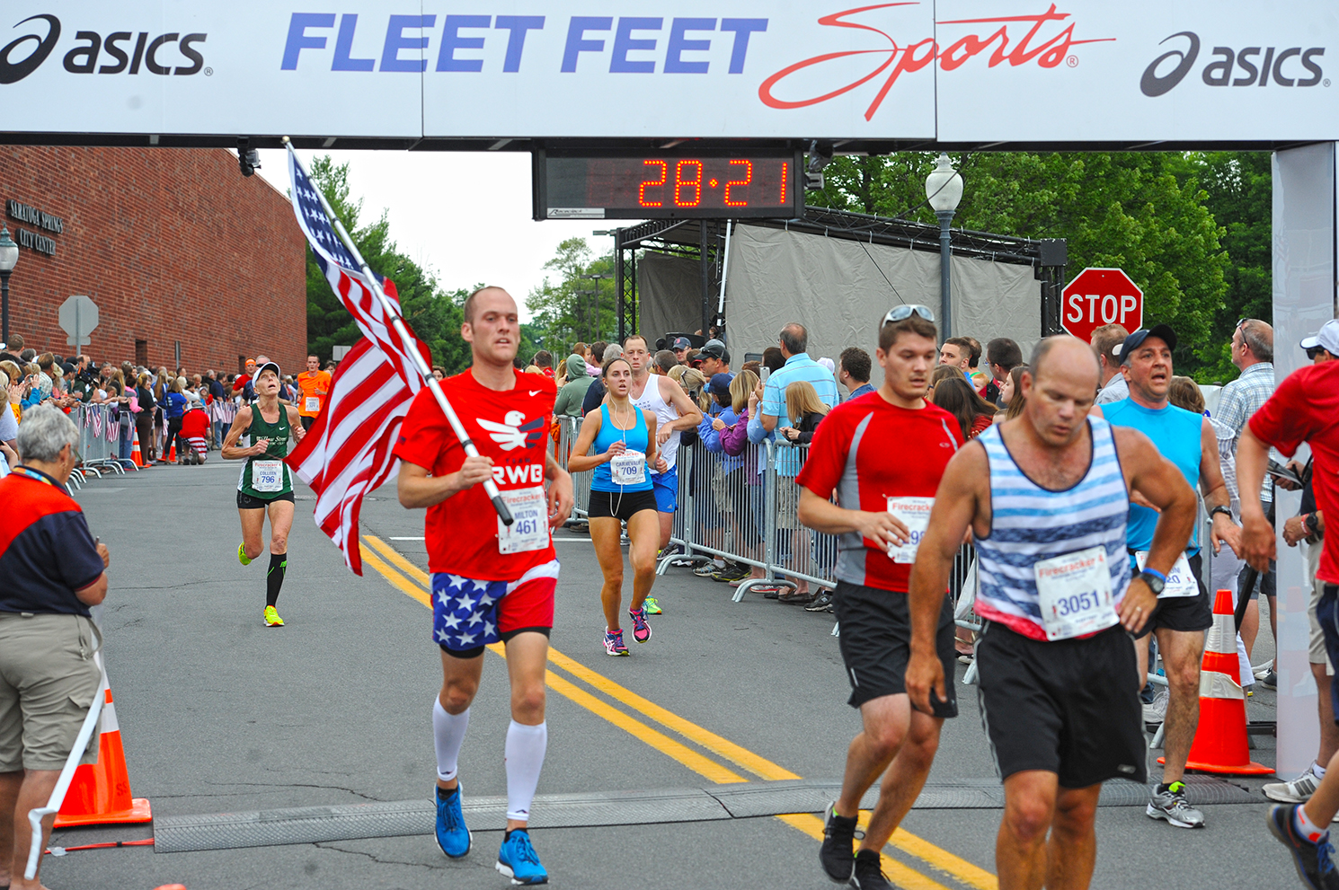 In the spirit of Independence Day, many  Firecracker 4  participants wear patriotic colors and some carry flags as they run the course.   Dave Harmon
