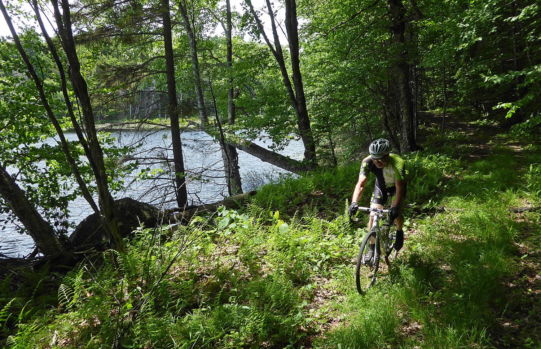 Don Massone rides near the lake shore amid ferns and trees. © Dave Kraus/ Krausgrafik.com