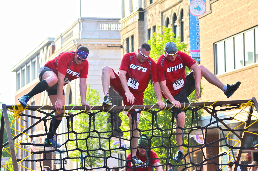 Tackling one of many obstacles in the Glens Falls Urban Assault.
