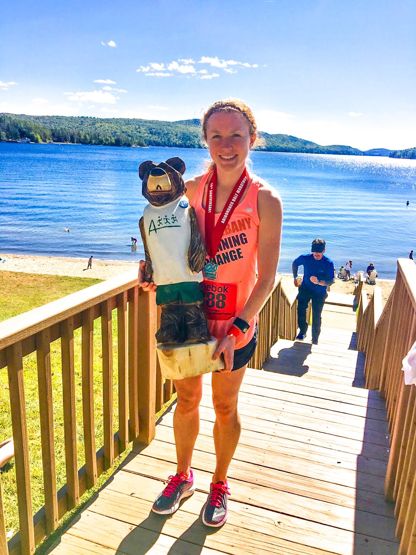 2016 Adirondack Half Marathon winner, Christine Coughlin of Latham, with her hand-carved Adirondack bear.
