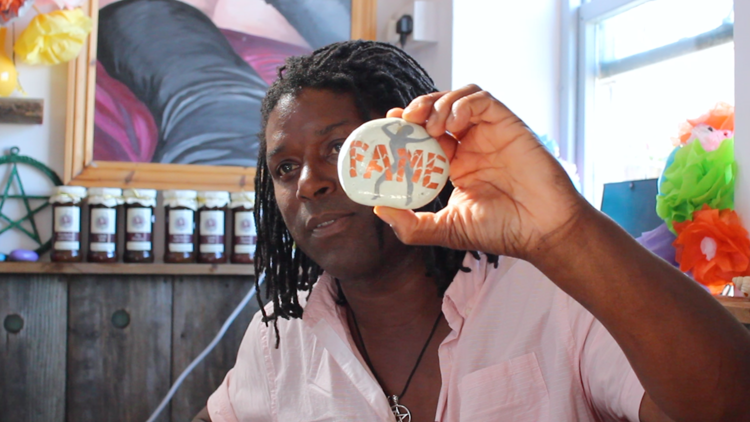 Peter St Ange of the Sea Cafe Coffee Shop in Deal Kent shows his stone painted to symbolise the fallacy of fame. It shows a silver figure on a white background with FAME painted in orange.