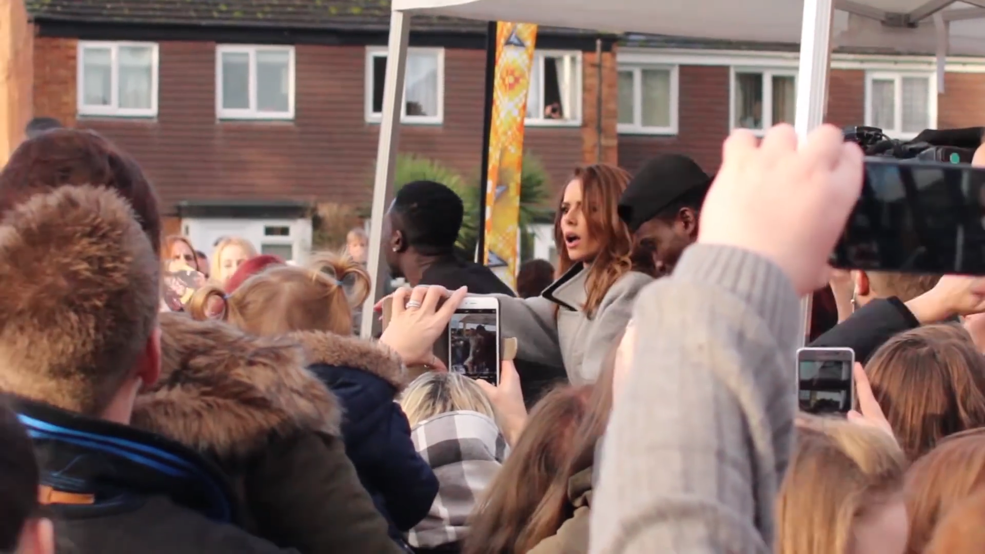 Reggie and Bollie dance with Cheryl Cole on a stage in a Farnborough Housing Estate for the XFactor.