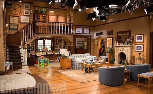 Which sitcom includes this living room with a very prominent staircase?