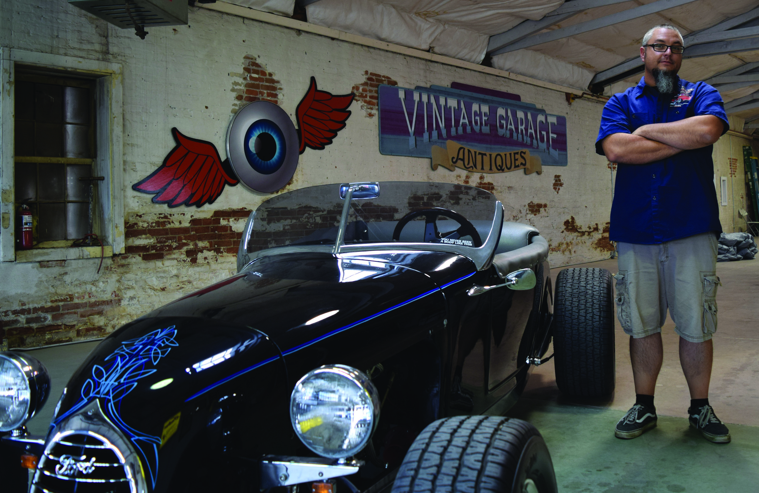 Ion Graphics owner Matt Beckner, 38, stands with a Ford from the 30s that he pinstriped for a client. The process took roughly four hours and five years of practice. Photo by Jefferson Geiger.