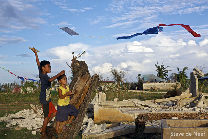 A pair of boys fly kites amid the ruins of Madridejos.