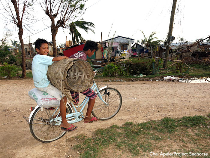 A pair of boys transport rebuilding materials by bike through their village. Photo: Chai Apale/Project Seahorse
