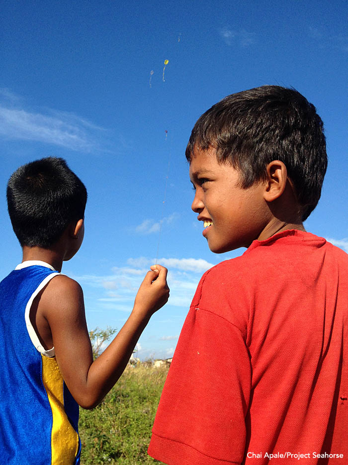 A sign of hope if there ever was one: A pair of boys fly homemade kits over what's left of their village. Photo: Chai Apale/Project Seahorse