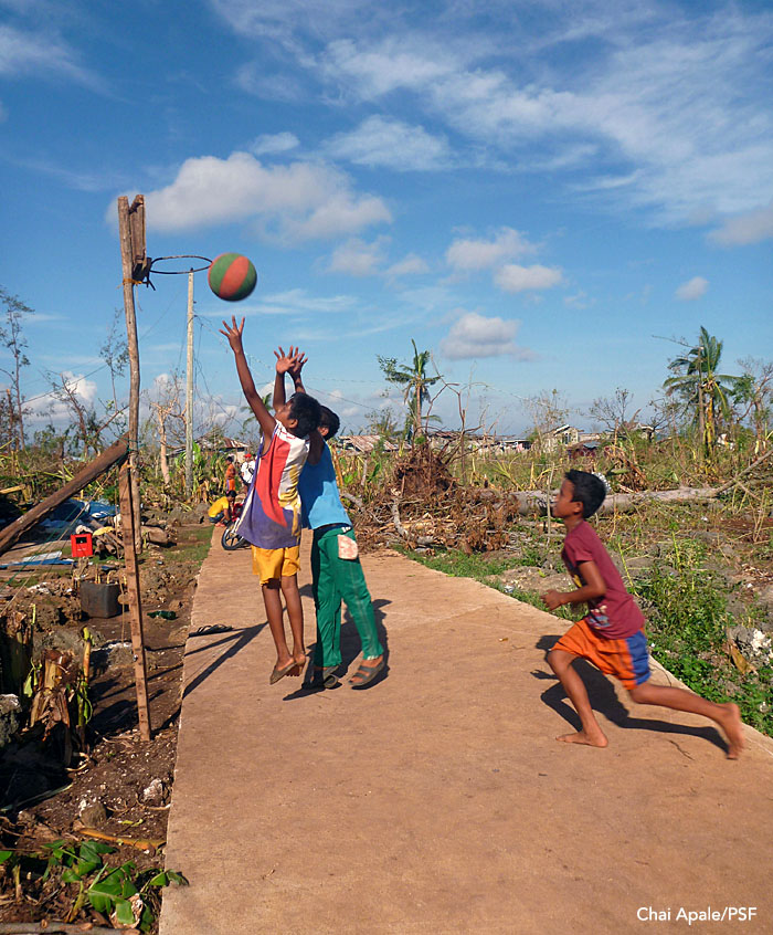 Signs of hope: Amid all of the destruction, life goes on. Boys play pickup basketball outside a village. Panay, Philippines.  Photo: Chai Apale/Project Seahorse