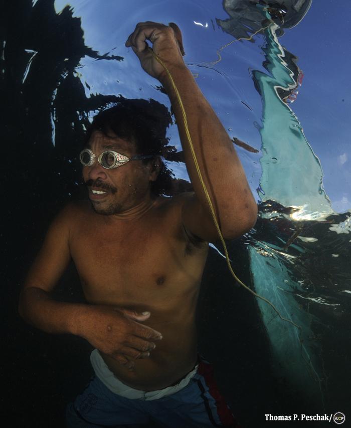 Swimming over a reef, a local lantern fisher pulls his boat behind him. Near handumon marine reserve, Danajon Bank.