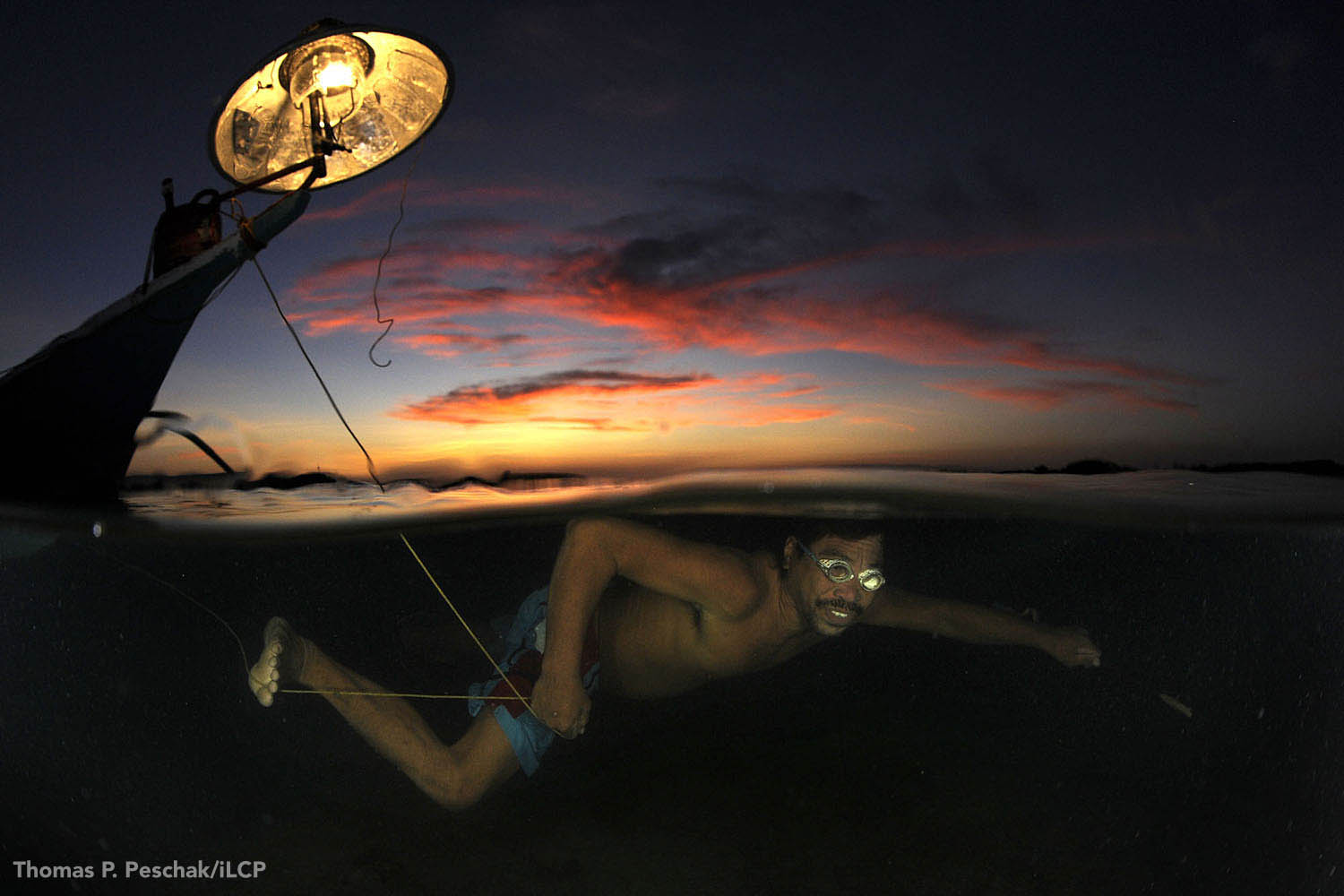 Equipped with homemade gear, this fisher will hunt all night for a meagre catch, including, if he's lucky, a seahorse or two. Lantern fishing is a traditional method that is slowly being replaced by more destructive practices.   Thomas P. Peschak/iLCP