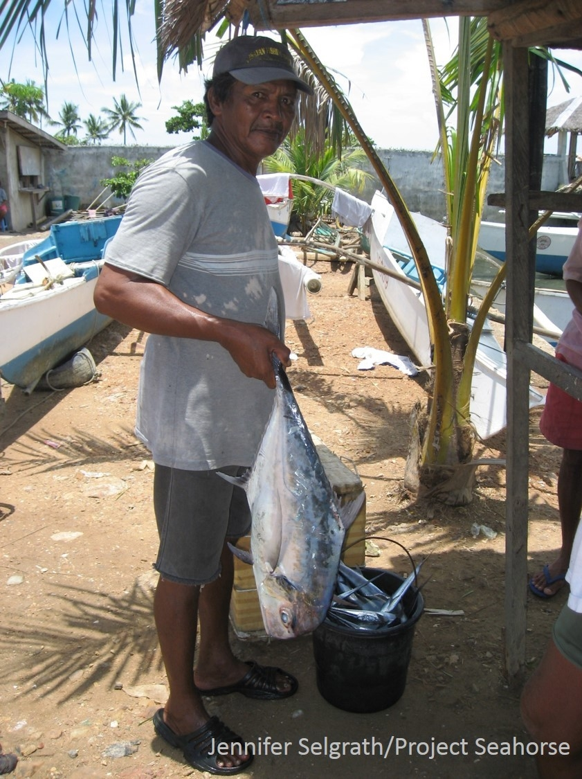 A local fish trader shows off some of the fish he bought from small-scale fishers.