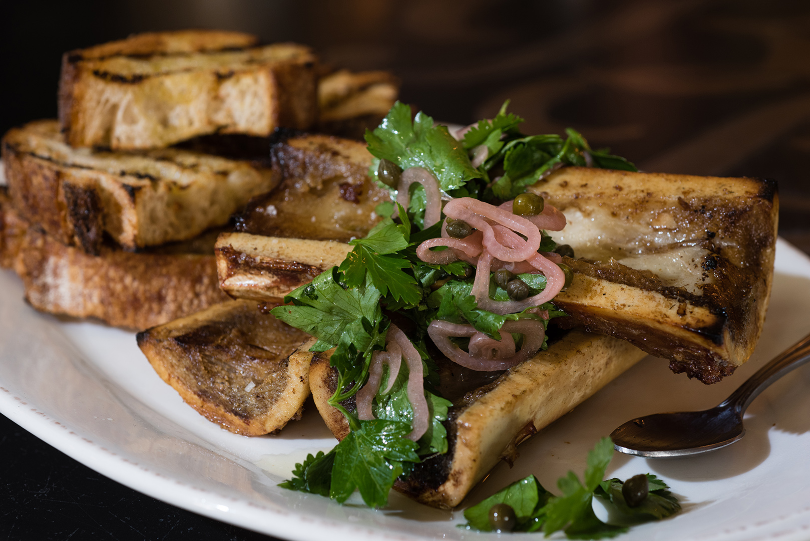 Smoked bone marrow with capers, shallots, herbs and crispy grilled bread. (Dustin Franz/The Washington Post)