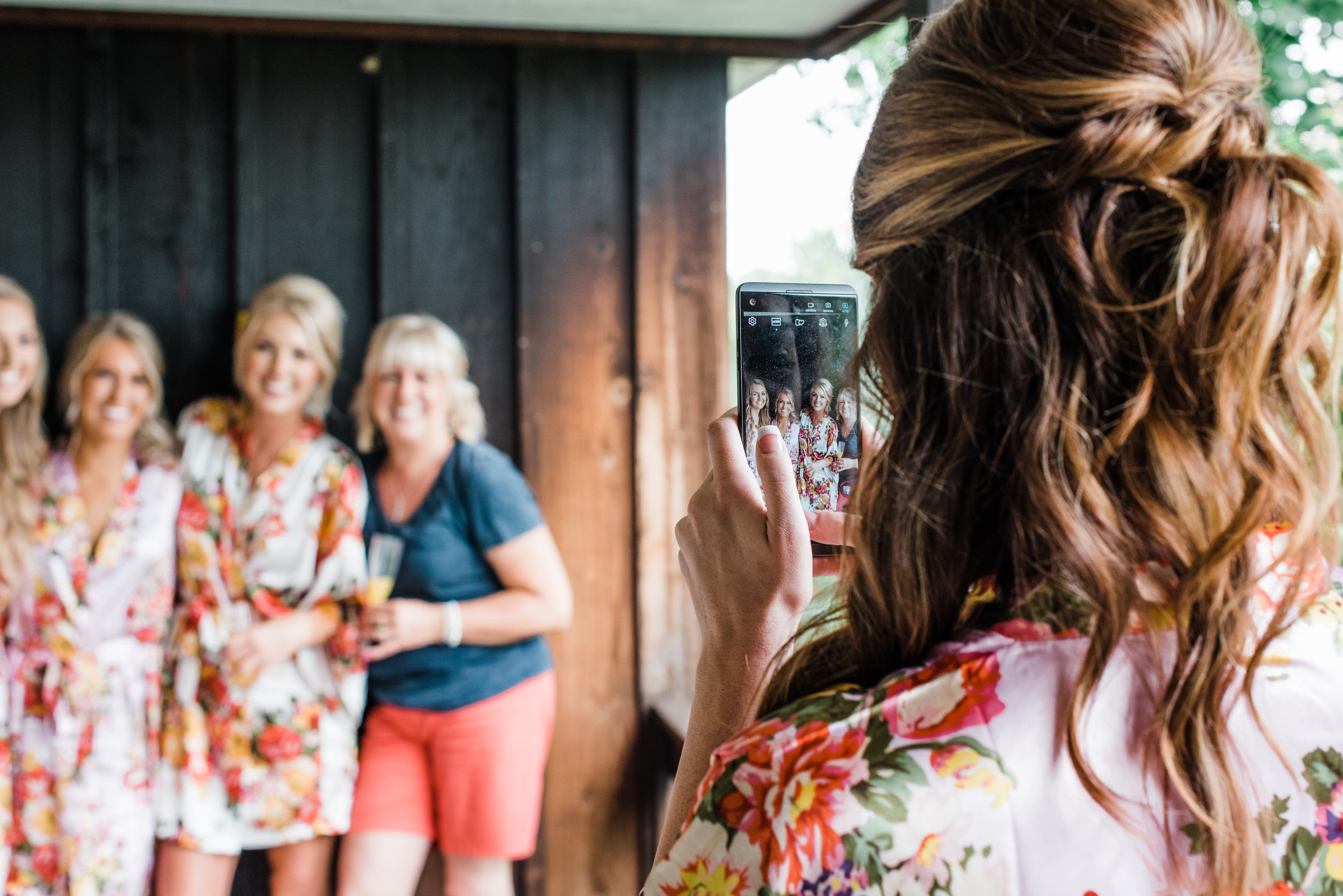 bridesmaid takes photo of bride at wedding venue
