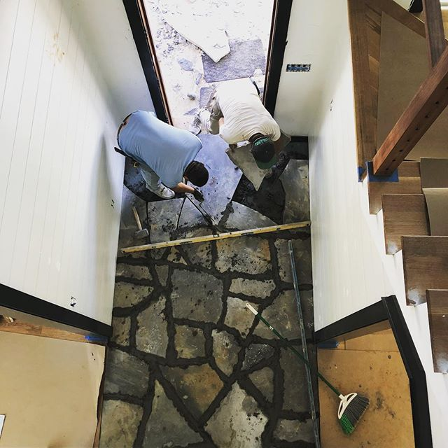 """The guys laying an interior flagstone entry. This type of floor is about 2 1/2"""" thick and heavy so you have to plan ahead during framing to get your stonework to have proper structural support and to finish flush with the surrounding floors. #stonework #interiors #flooring"""