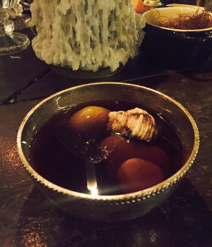 Mezcal cocktail literally on the rocks with a snail shell