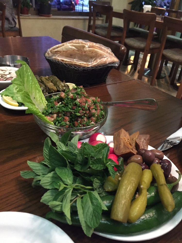 Olives, pickles, tabbouleh, and stuffed grape leaves