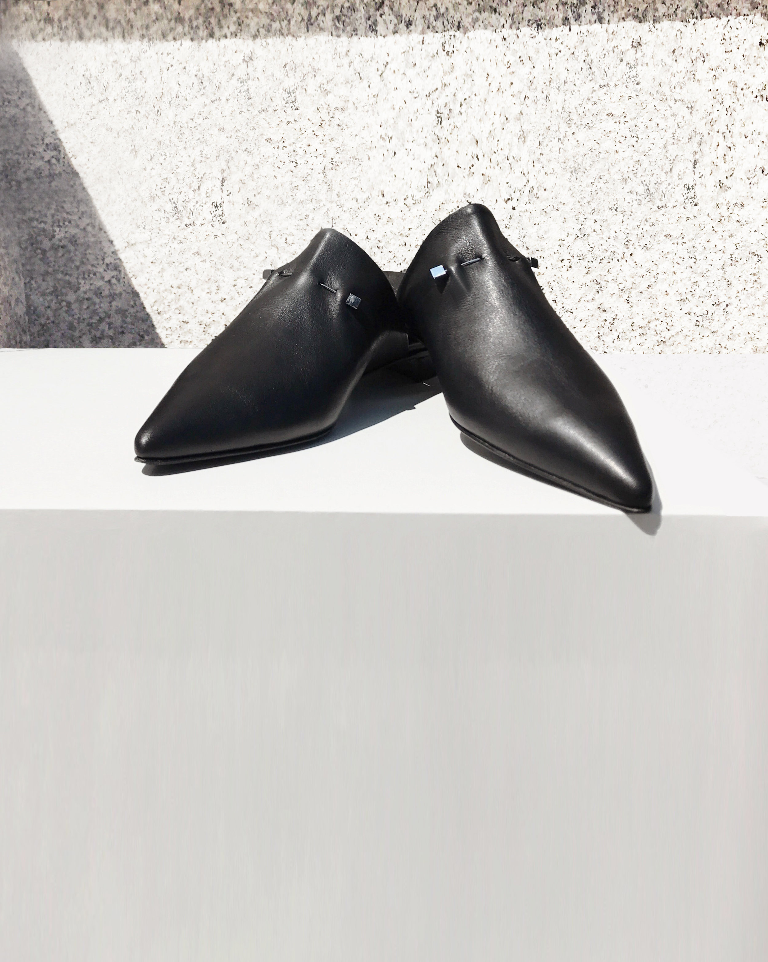 HANDCRAFTED SHOES - Black leather pointy-toe slipper with signature hardware for timeless chic