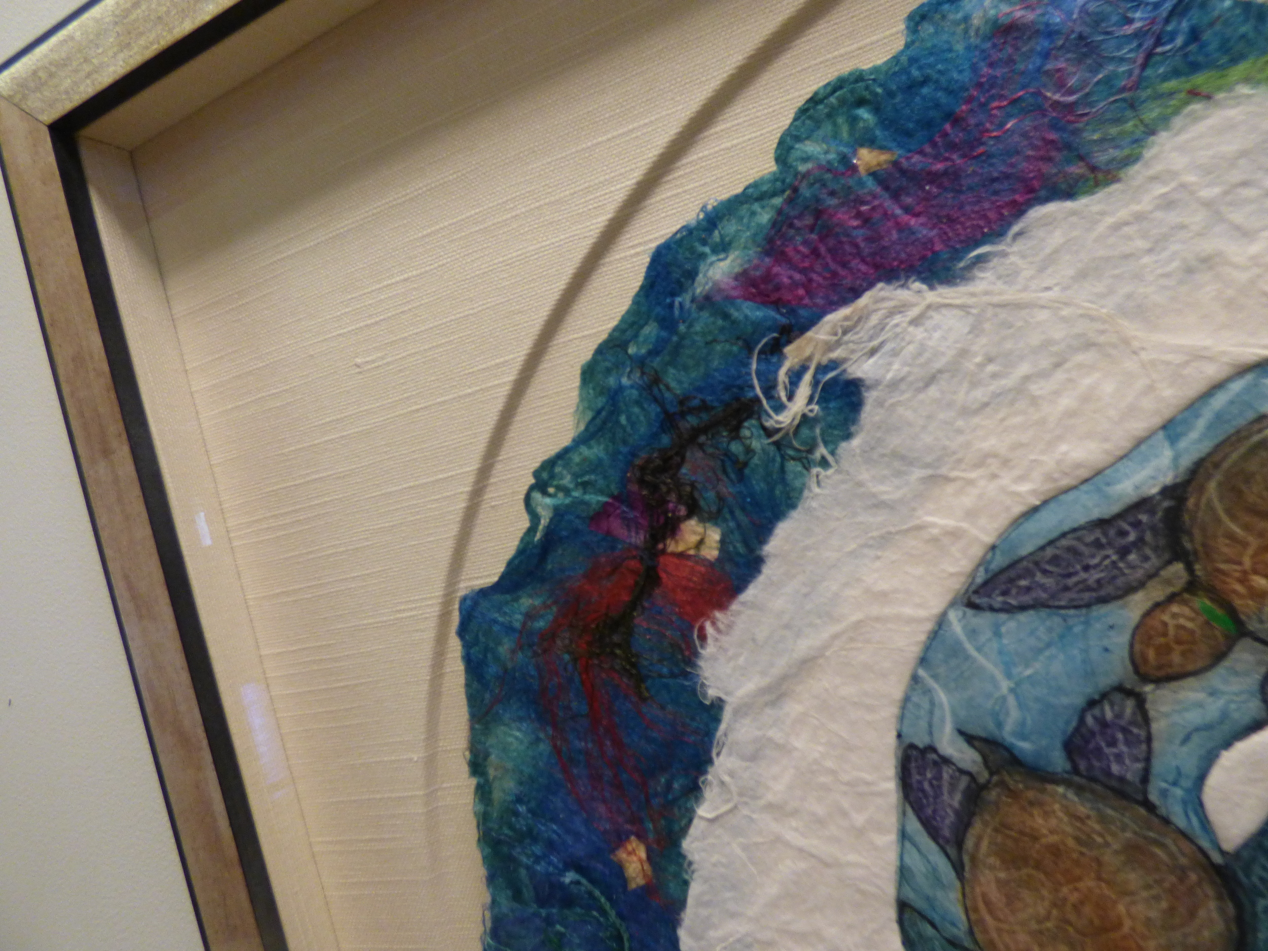 A circle cut out to mimic the art, was overlayed with fine fabric and expertly assembled by our Master Framer.
