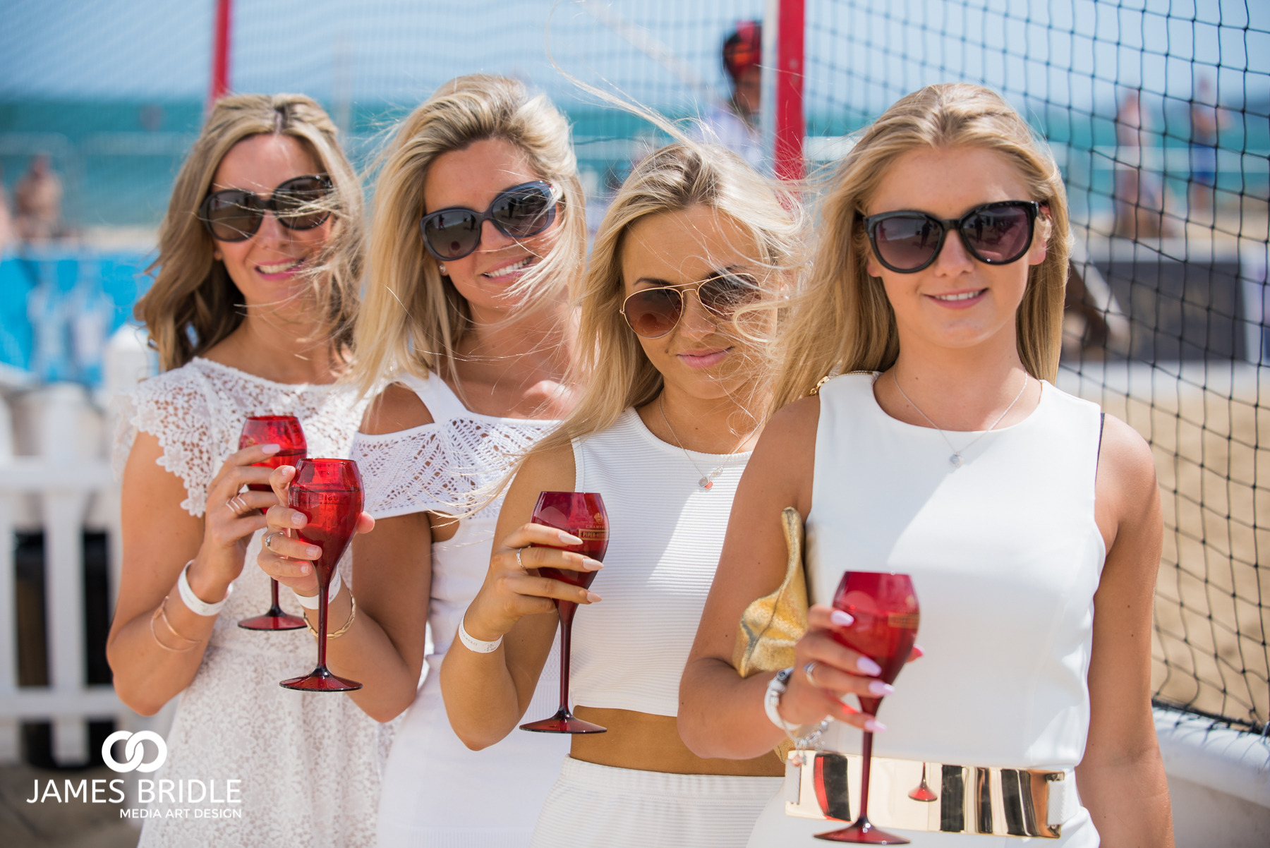 Ladies getting their glasses of piper heidsieck ready for the 3PM start of the Sand Polo - Saturday