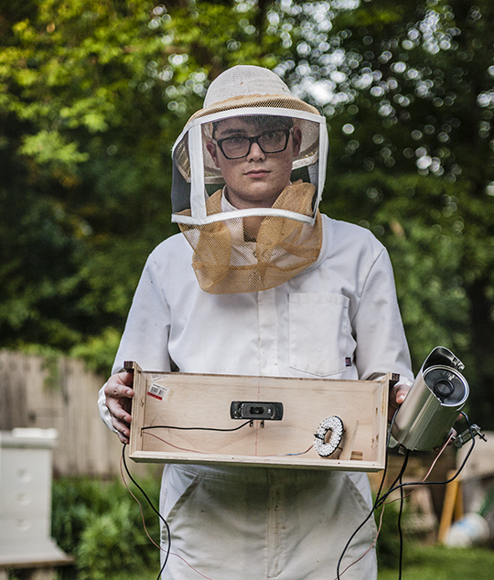 Wynn Geary holds monitoring equipment for his smart beehive. Right: Action in the hive, seen on his laptop, will one day be streamed on a public website | photos by Addison Geary