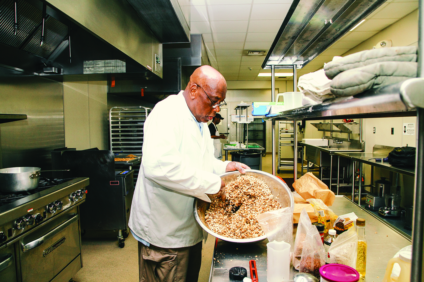 Victor Michael hand-mixes a batch of hisPhilly Delcious Granola|  Photo by Stephen Dyer