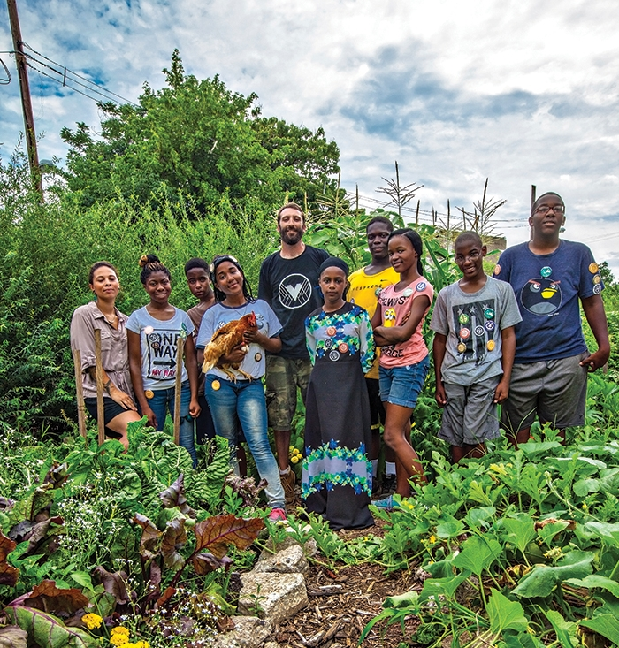 PhillyEarth permaculture students at the Village of Arts and Humanities stand with their teacher, Jon Hopkins (center) in the middle of their garden |   photos by Jared Gruenwald