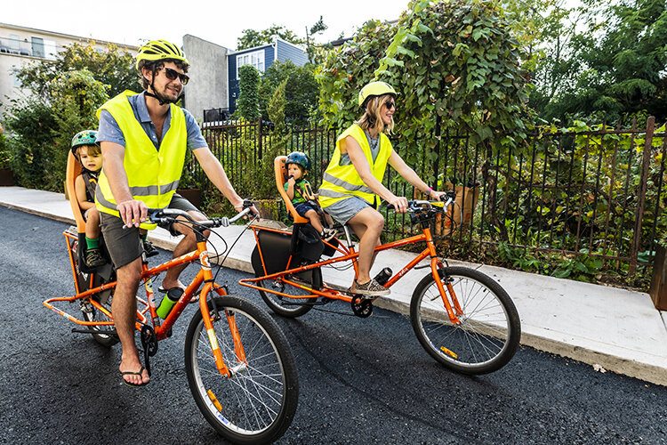 Jonathan Purtle and Sara Hirschler make themselves more visible to drivers with orange bicycles and yellow reflective gear. Photography by Linette Kielinski