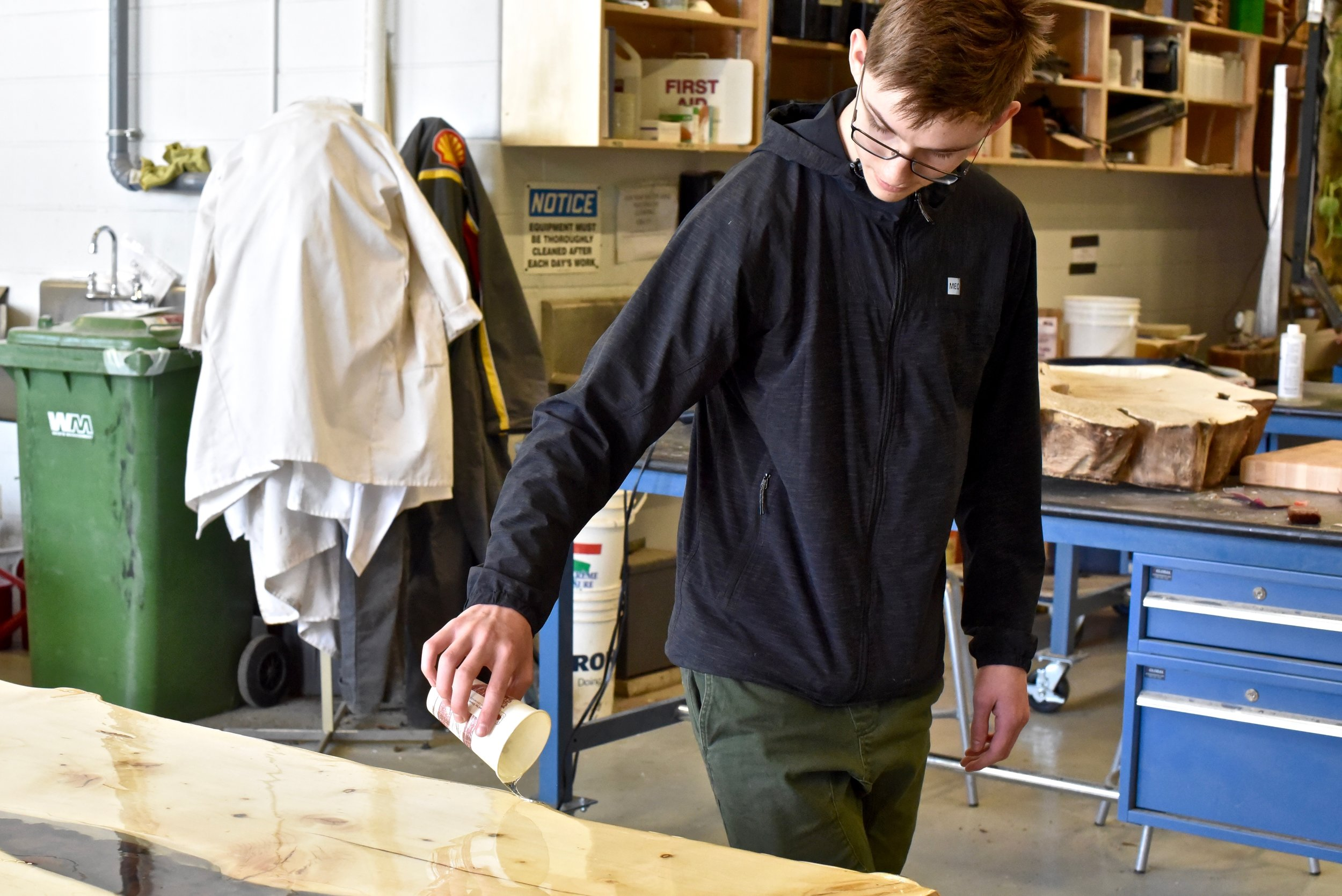 several students cut and sand wood into rustic, live-edge benches and tables — using only recycled or upcycled wood, of course. (Sarah Lawrynuik)