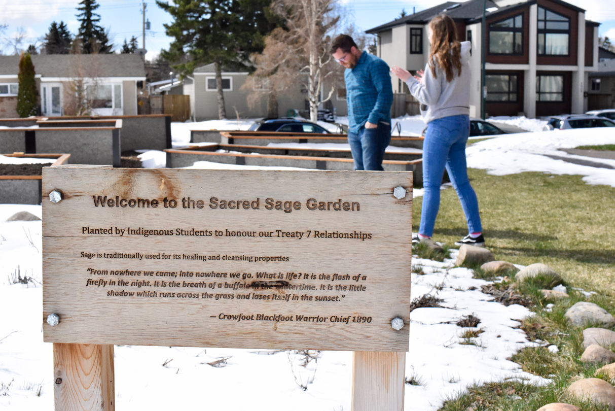 Kiera Williams, 16, stands with her teacher Adam Robb in a new community garden as they plan out where to put benches (made by the class) to encourage locals to come and spend time in the garden. (Sarah Lawrynuik/The Narwhal)