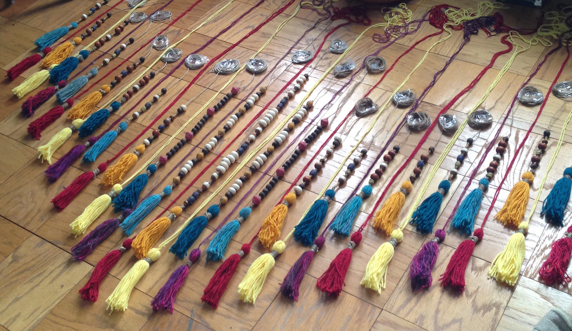 Finally,I laid it all out on my living room floor exactly how I was going to hang it up. The top row has beads on twine because the yarn alone is not strong enough to hold the weight of the beads. The bottom row is only yarn and tassels, no beads.