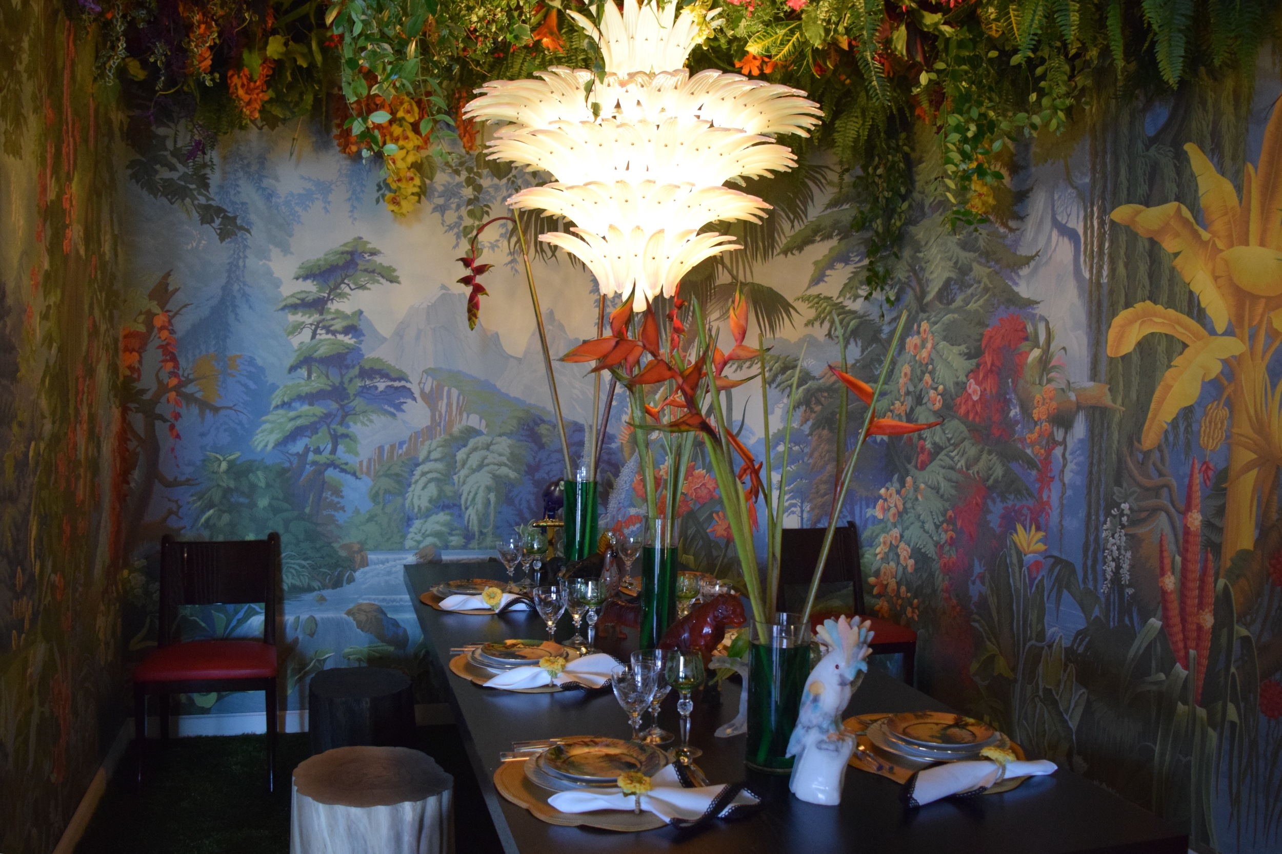 """""""Christian Liagre is known for amazingly chic and sleek woodwork, so this space translates that into something more vibrant that displays the furniture in a new light with de Gournay's 'Le Eden' wallpaper transforming the room into a rainforest."""""""