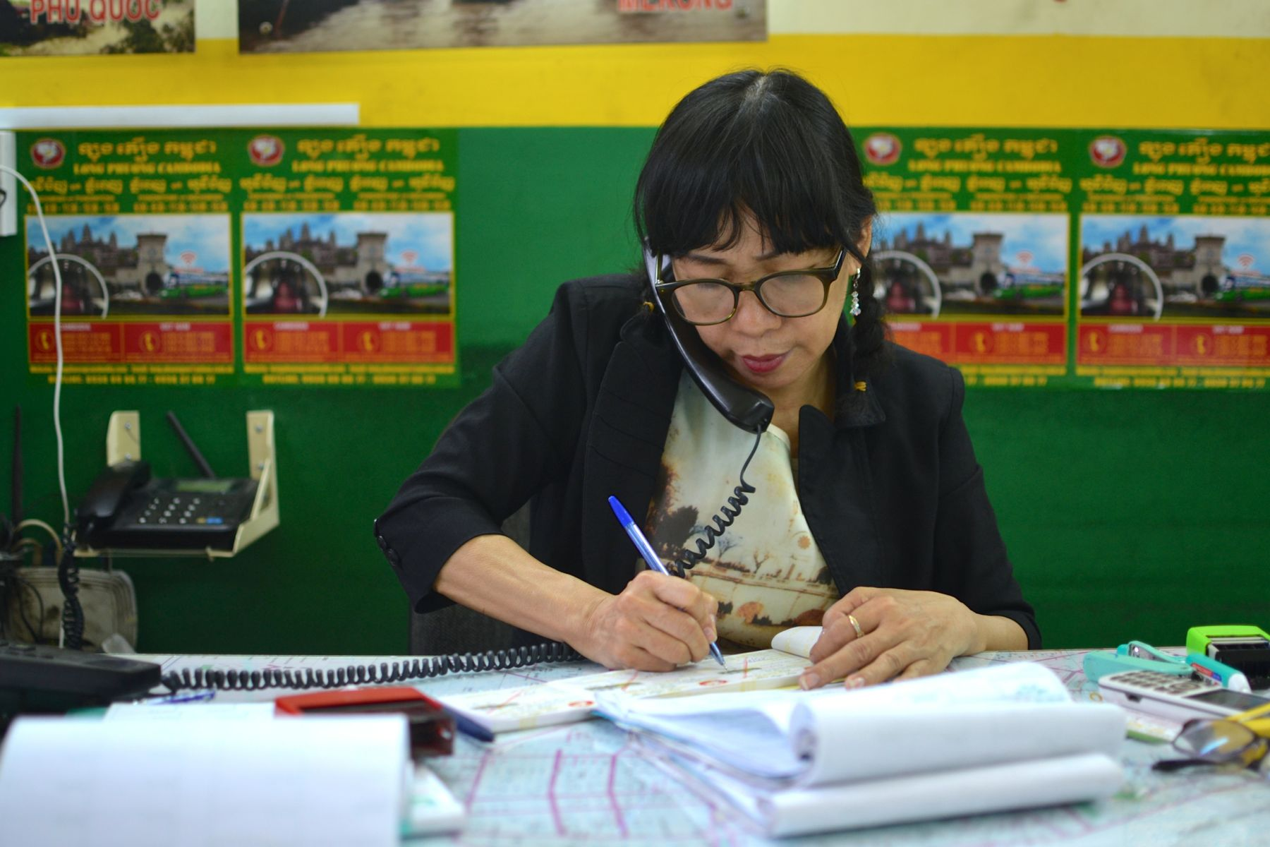 A Vietnamese travel agent - multitasking and just as busy as the ones back home