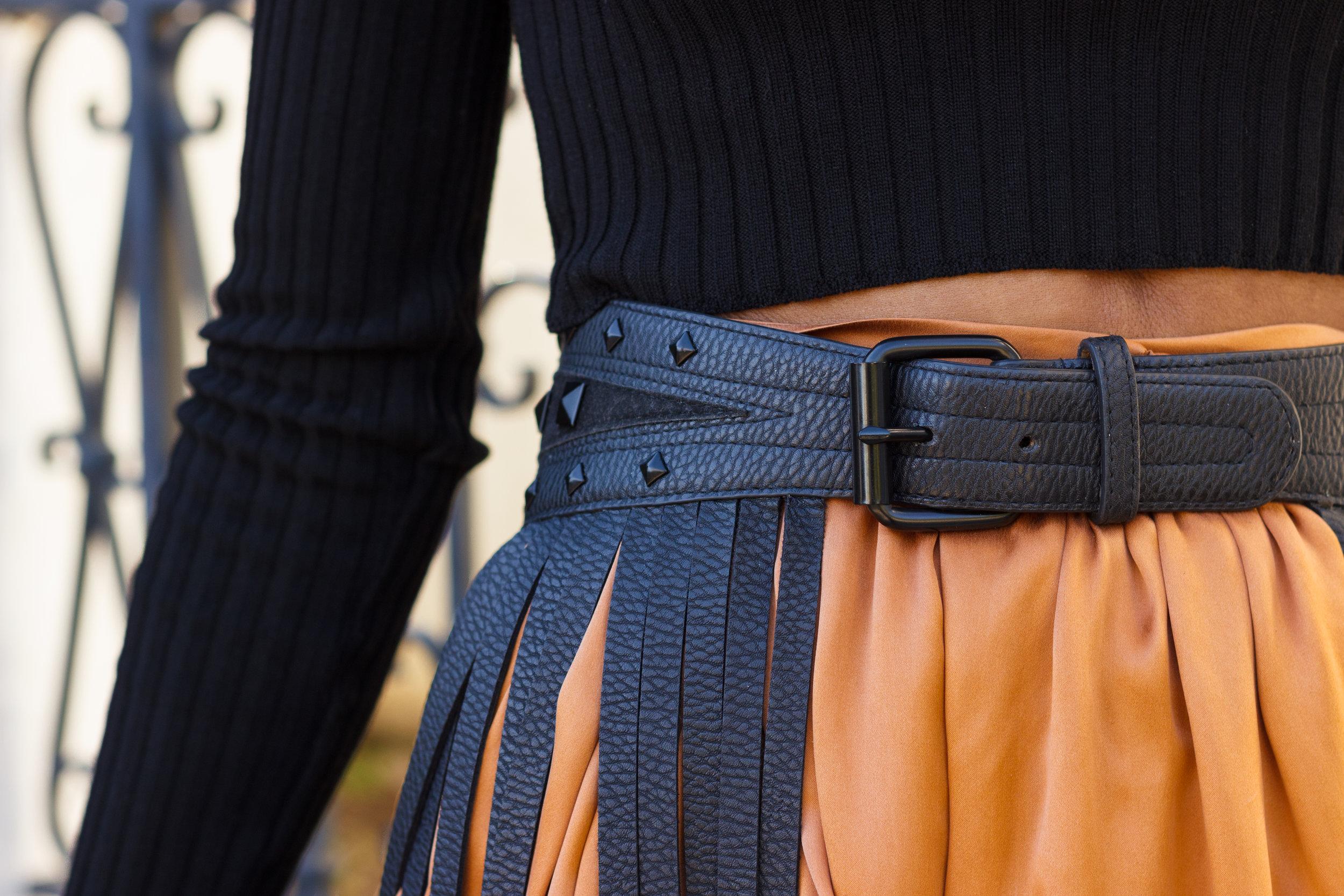 Detail image of the vintage black faux leather fringe belt.