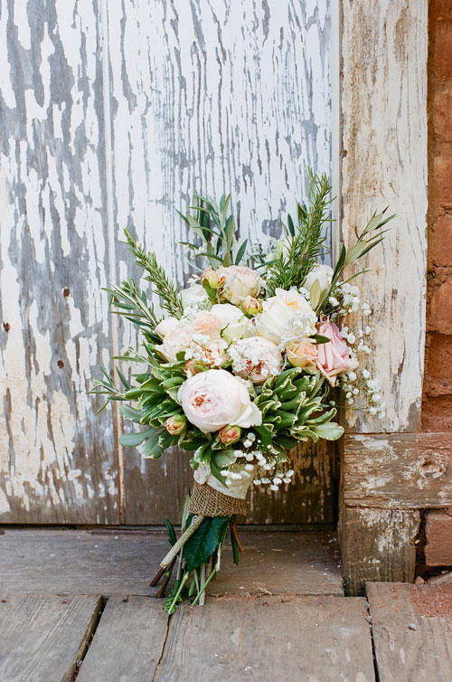 Kate Healey Bridal Bouquet Leaning Against a Rustic Wall