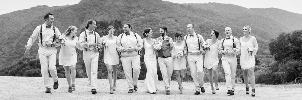 Friends at a wedding walk arm in arm in Big Sur