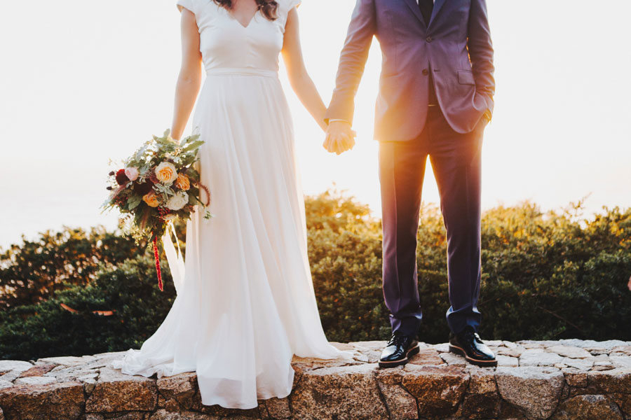 Groom and Bride Holding Hands with Flowers by Kate Healey